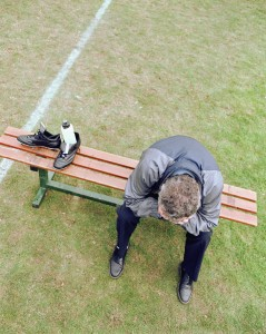 Man on bench with head in hands